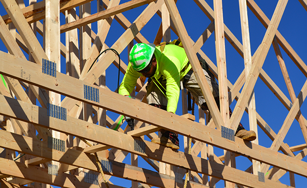 A construction worker in safety gear working on roof trusses at a jobsite